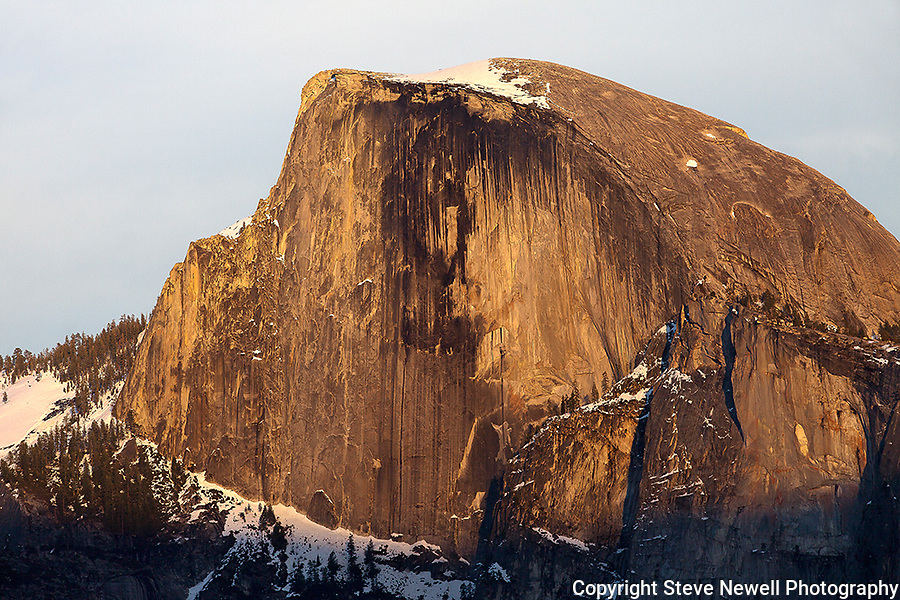"""""""Half Dome Close Up"""" Yosemite National Park, California. This photograph was taken a few minutes after the """"Sunset 2"""" image. I have posted a series of three photographs of this sunset along with an artistic version where I smoothed out the texture of the rock. Capturing Half Dome at sunset really showcases the spectacular colors of its monolithic face.  45,000 people a year climb the famous cables to the summit. I took this picture on my way back down from hiking Yosemite Falls Waterfall."""