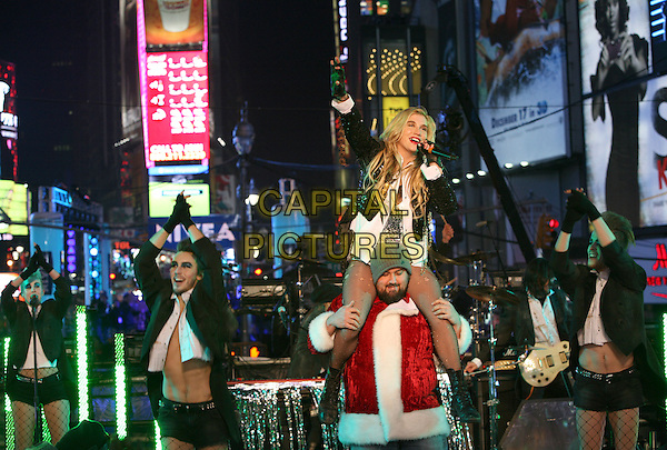 KESHA (Ke$ha aka Kesha Rose Sebert).New Years Eve 2011 Times Square New York City, New York, NY, USA,  31st December 2011..full length performing live on stage music concert gig ripped fishnet tights gloves black jacket  white shirt silver sequined sequin body leotard  fingerless on shoulders santa outfit boots arm raised up being carried microphone singing .CAP/ADM/PZ.©Paul Zimmerman/AdMedia/Capital Pictures.