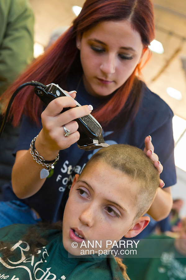 JOSEPH ROSENTHAL, 11, of Merrick, has his head shaved by KELSEY BAZAREWSAKI, a junior who takes cosmetology at Calhoun High School, at the school's St. Baldrick's fund raising event. The Long Island school exceeded its goal of raising $50,000 for childhood cancer research. Plus, many ponytails cut off will be donated to Locks of Love foundation, which collects hair donations to make wigs for children who lost their hair due to medical reasons.