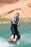 Mature female with smile wakeboarding for first time, Lake Powell