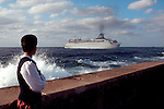 Havana, Cuba, Cuban woman stares at a departing ocean liner leaving Havana harbor for the rest of the world, East end of the Malecon, Caribbean Sea, Central America