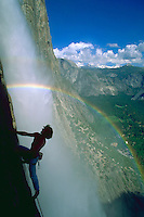 A rainbow appears to surround a climber beside Yosemite Falls in Yosemite National Park, California with snow covered mountains, clouds and blue sky in the distance.