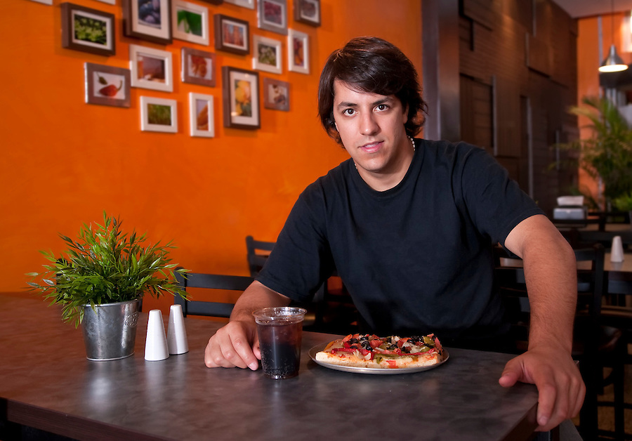 Young man seated in a restaurant with a slice of pizza and beverage.