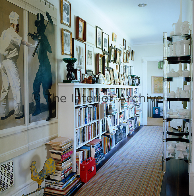 The upstairs landing doubles as a library and features a wall covered in family photographs, a painting by Matthew Benedict and a collection of milk glass on an etagere