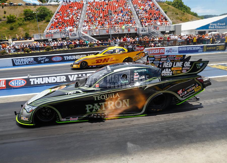 Jun 19, 2016; Bristol, TN, USA; NHRA funny car driver Alexis DeJoria (near) races alongside teammate Del Worsham during the Thunder Valley Nationals at Bristol Dragway. Mandatory Credit: Mark J. Rebilas-USA TODAY Sports