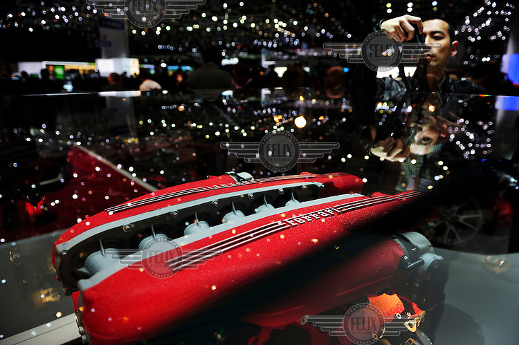 A guest takes a photograph of an Engine on display at the Ferrari stand at the Geneva Motor Show.