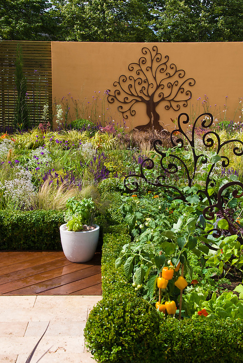 Rustic Tree Garden Ornament On Wall And In Vegetable Next To Patio Deck With
