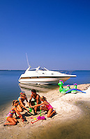 Family playing on beach island reached by boat.