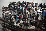 KISANGANI, DEMOCRATIC REPUBLIC OF CONGO MARCH 8: Hundreds of travelers offload goods as they have just arrived after four-week journey on an overcrowded boat from Kinshasa on March 8, 2006 in Kisangani, in Congo, DRC. The Congo River is a lifeline for millions of people, who depend on it for transport and trade. The journey from Kinshasa to Kisangani is about 1750 kilometers, and it takes from 3-7 weeks on the river, depending on the boat. During the Mobuto era, big boats run by the state company ONATRA dominated the traffic on the river. These boats had cabins and restaurants etc. All the boats are now private and are mainly barges that transport goods. The crews sell tickets to passengers who travel in very bad conditions, mixing passengers with animals, goods and only about two toilets for five hundred passengers. The conditions on the boats often resemble conditions in a refugee camp. Congo is planning to hold general elections by July 2006, the first democratic elections in forty years. (Photo by Per-Anders Pettersson)
