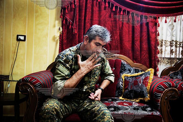 Kurdish People's Protection Unit (YPG) spokesman Colonel Redur Xedlil smokes a cigarette.