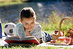 Young girl (8 years old) reading a book lying down on a blanket at a picnic summer reading Lake Pleasant Bothell Washington State USA MR