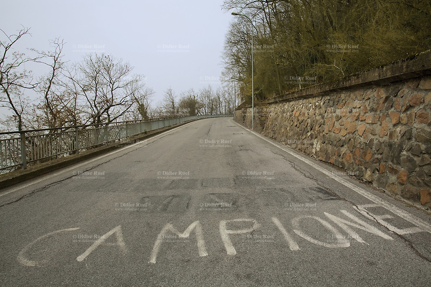Italy. Lombardy region. Campione d'Italia. Concrete secondary road with white painted words written on the ground. Campione d'Italia is occupying an enclave within the Swiss canton of Ticino. 1.03.2008 © 2008 Didier Ruef .