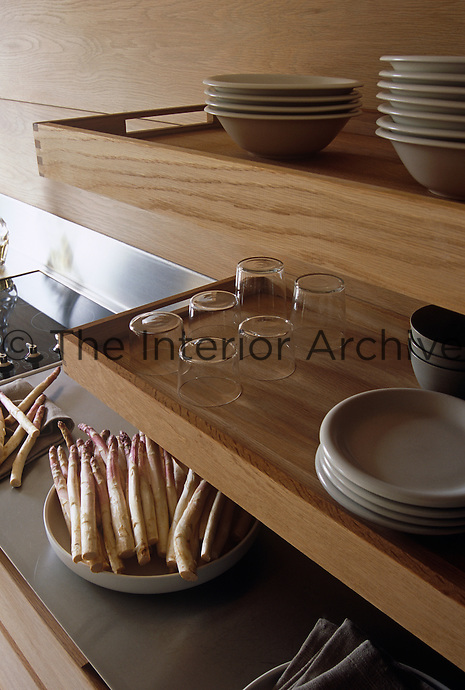 Crockery and glassware is stored on contemporary wooden shelves which resemble trays