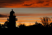 Katiki Point Lighthouse in silhouette at sunset,  near Moeraki Villiage, Coastal Otago, South Island, New Zealand - stock photo, canvas, fine art print