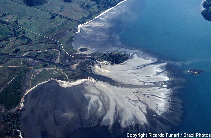 Aerial view of the base level of a river, the lowest point to which it can flow, often referred to as the 'mouth of the river', as it pours out into ocean, forming a sand bank or river delta, a landform that forms from deposition of sediment carried by a river as the flow leaves its mouth and enters slower-moving or standing water.