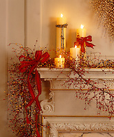 Corner of a Victorian carved mantelpiece draped in Christmas garlands and red ribbons illuminated by the flames of a number of candles of varied heights