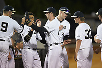 Wake Forest Demon Deacons relief pitcher Antonio Menendez (27) is greeted by his teammates as he is removed from the game against the North Carolina State Wolfpack at David F. Couch Ballpark on April 18, 2019 in  Winston-Salem, North Carolina. The Demon Deacons defeated the Wolfpack 7-3. (Brian Westerholt/Four Seam Images)