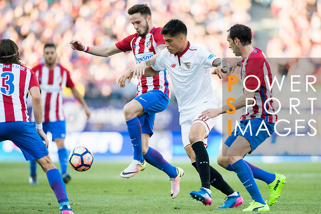 Carlos Joaquin Correa (c) of Sevilla FC battles for the ball with Saul Niguez Esclapez and Diego Roberto Godin Leal of Atletico de Madrid during their La Liga match between Atletico de Madrid and Sevilla FC at the Estadio Vicente Calderon on 19 March 2017 in Madrid, Spain. Photo by Diego Gonzalez Souto / Power Sport Images