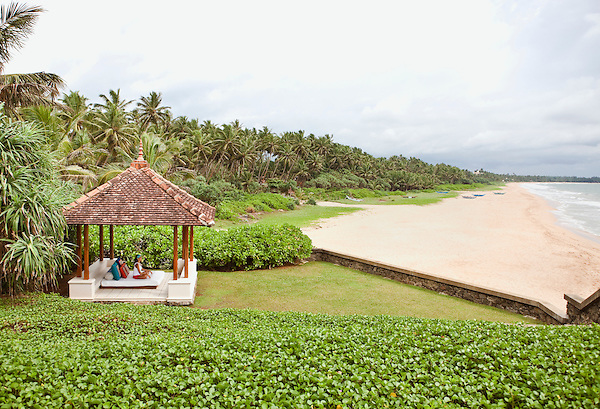 A woman relaxes on a daybed in an ocean-front cabana at Saman Villas, Aturuwella, Bentota, Sri Lanka.