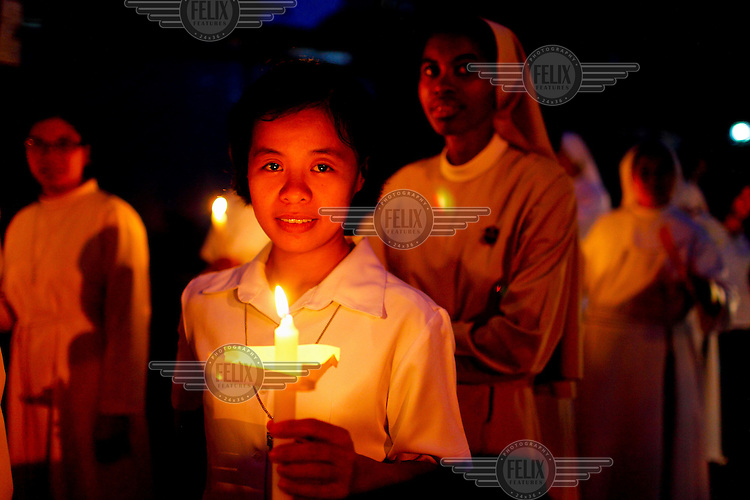 A woman carries a burning candle during a church service.