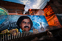"A large mural artwork, depicting the drug lord Pablo Escobar, is seen painted on the wall in the Pablo Escobar neighborhood in Medellín, Colombia, 6 December 2017. Twenty five years after Pablo Escobar's death, the legacy of the Medellín Cartel leader is alive and flourishing. Although many Colombians who lived through the decades of drug wars, assassinations, kidnappings, reject Pablo Escobar's cult and his celebrity status, there is a significant number of Colombians who admire him, worshipping the questionable ""Robin Hood"" image he had. Moreover, in the recent years, the popular ""Narcos"" TV series has inspired thousands of tourists to visit Medellín, creating a booming business for many but causing a controversial rise of narco-tourism."