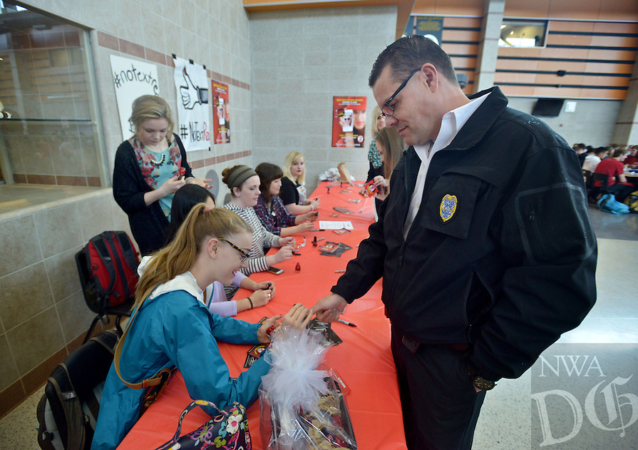 NWA Democrat-Gazette/BEN GOFF -- 03/13/15 Katie Andrews, 15, a Student Council volunteer, paints the thumbnail of Bentonville Police Chief Jon Simpson with No Text Red nail polish in the North cafeteria at Bentonville High School on Friday Mar. 13, 2015. Students, faculty and guests signed pledges not to text while driving before having their thumbnails painted red as a reminder during the event organized by the school's PTO in partnership with SinfulColors, makers of No Text Red. Students from the Student Council, DECA club, the National Honor Society and special education classes volunteered during their lunch breaks to help make the event possible.