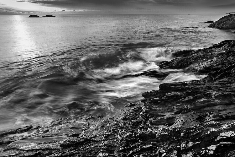 British coastal scene with swirling waves on rocky shoreline