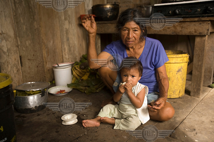 An elderly woman sits with her grandson in her kitchen near the Quichua community of San Pedro Sumino.