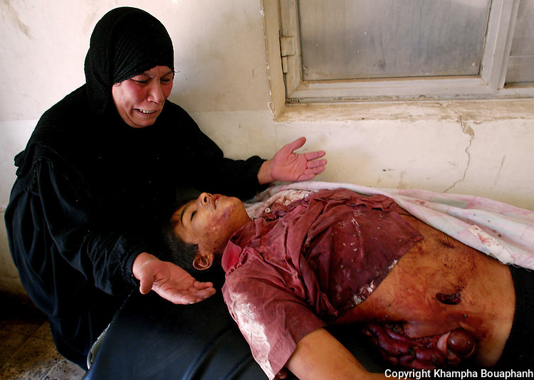 Mozah Abud grieves over her 15-year-old son Samah Hussein, who was killed when a car bomb detonated south of Baghdad near Camp Cuervo on June 13, 2004.   The blast killed least 12 Iraqi civilians and wounded several others. (photo by Khampha Bouaphanh)