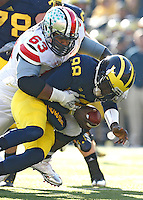 Ohio State Buckeyes defensive lineman Michael Bennett (63) takes down Michigan Wolverines quarterback Devin Gardner (98) in second half action at Michigan Stadium in Ann Arbor, MI on November 30, 2013.  (Chris Russell/Dispatch Photo)