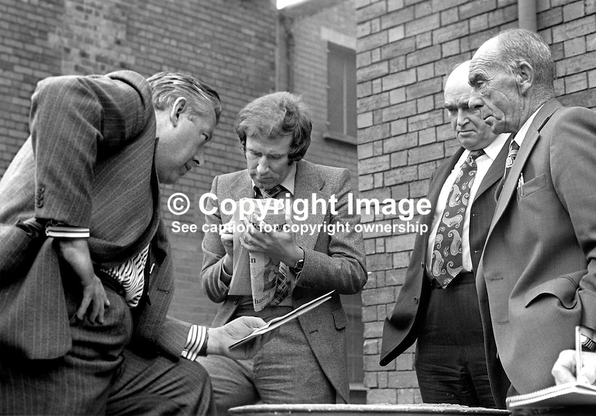 Andrew Neil, journalist, reporting for the Economist, conducts an impromptu Press Conference with October 1974 UK General Election candidates, from left, Rev Ian Paisley, Harry West and John McQuade. Paisley and West were on the Shankill Road, Belfast, supporting the local West Belfast candidate McQuade. Mr Neil went on to become editor of the London Sunday Times from 1983 to 1994. 197410090526c<br />