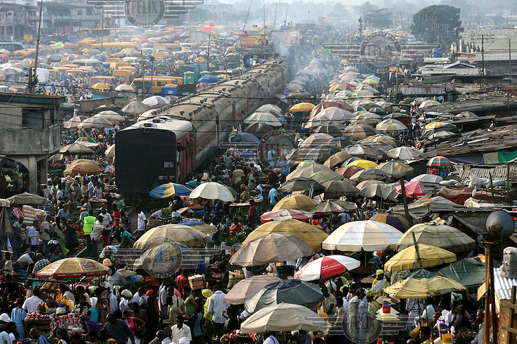 A train moves through the centre as people walk in between transport buses in Oshodi open market in Lagos.