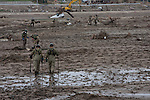Soldiers from the Japanese Self Defense Force (JSDF) search for bodies and other items in the mud near Minami Soma, Fukushima, Japan Tuesday, May 3rd 2011. Minami Soma is on the edge of the 20 kilometre exclusion zone around the Fukushima Daichi nuclear power station that was badly damaged in the earthquake and tsunami leading to explosioms and radiation leaks in the area.