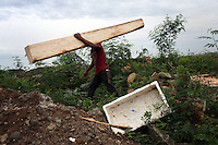 A worker carries a recently cut piece of timber near the shores of a reservoir in northern Jakarta. Trees are being cleared to enable to the expansion and dredging of the reservoir which is choked with pollution. It is hoped that this will help ease flooding in the local area.