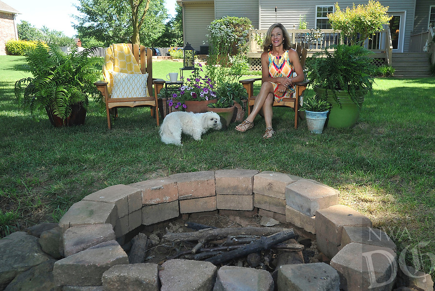 NWA Democrat-Gazette/MICHAEL WOODS --06/09/2015--w@NWAMICHAELW...  Tracy Byrd in her favorite space in her backyard with her dog D.J. at her Fayetteville home.