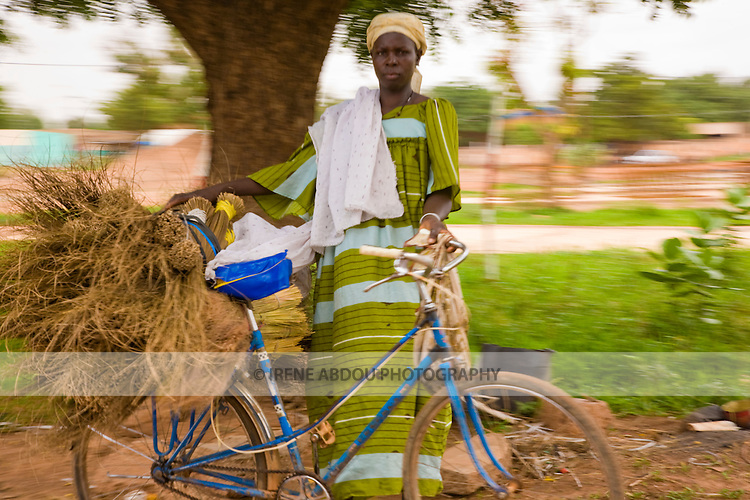 A woman stands by the side of the road in Ouagadougou, Burkina Faso, her bicycle loaded with straw brooms for sale.