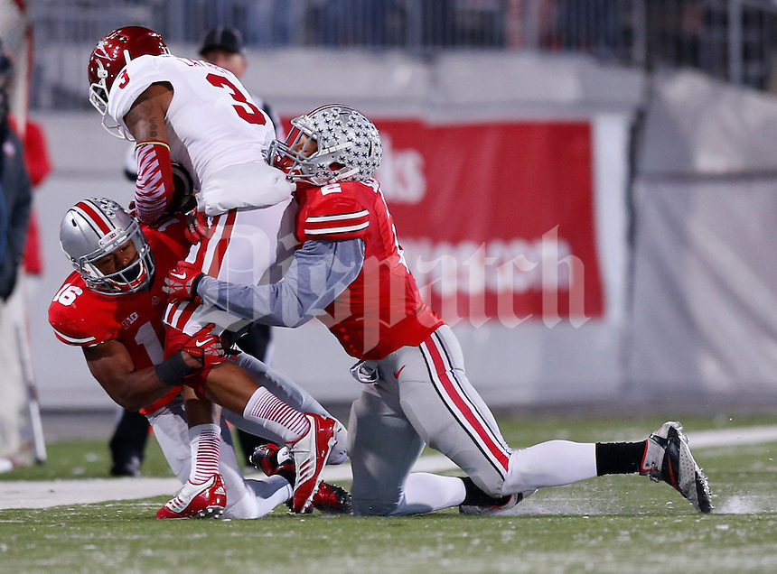 Ohio State Buckeyes safety Christian Bryant (2) and Ohio State Buckeyes defensive back Cam Burrows (16) take down Indiana Hoosiers wide receiver Cody Latimer (3) in the fourth quarter of the college football game between the Ohio State Buckeyes and the Indiana Hoosiers at Ohio Stadium in Columbus, Saturday afternoon, November 23, 2013. As of half time the Ohio State Buckeyes led the Indiana Hoosiers 42 - 14. (The Columbus Dispatch / Eamon Queeney)