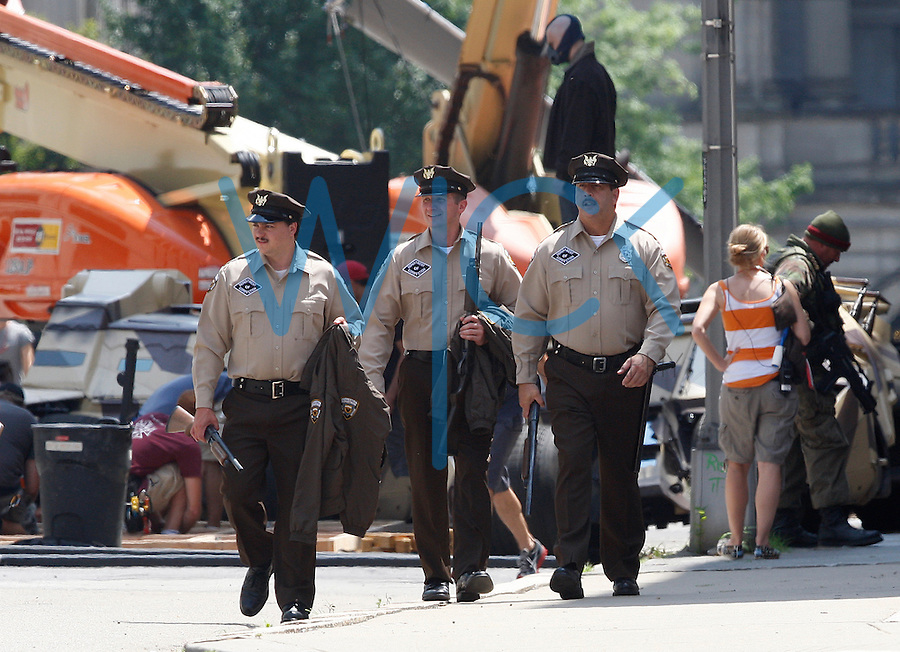 Cast members dressed as armed correctional facility guards walk around during the filming of the new Batman: Dark Knight Rises movie near the Carnegie Mellon University Software Engineering Institute building while actor Tom Hardy, who plays the villian, Bane, readies for a scene in the Pittsburgh neighborhood of Oakland on July 30, 2011.