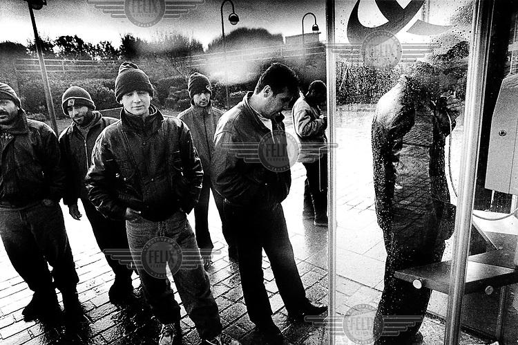 ©Piet den Blanken/Panos Pictures..France, Calais, november 2000.Illegale migranten In de rij voor een telefooncel in Sangatte..Vanuit een opvangcentrum in Sangatte lopen illegalen naar de haven van Calais. .In Calais proberen illegalen verstopt in vrachtwagens naar .Engeland, Groot Brittanni_, UK, te reizen. Mensensmokkel.