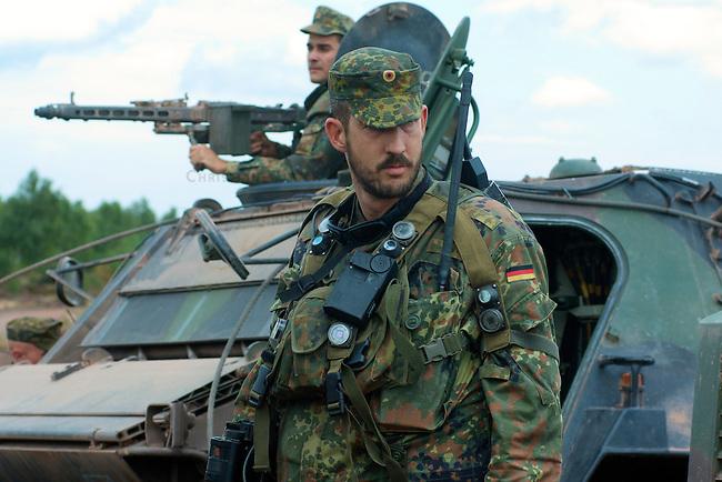 Quick Reaction Force, QRF, der Bundeswehr auf dem Truppenuebungsplatz Colbitz-Letzlinger Heide in Sachsen-Anhalt.<br />Am Freitag den 28. August 2009 wurde im Zuge einer Pressevorfuehrung auf dem Gelaende des Gefechtsuebungszentrum Heer, GUEZ, eine Uebung der ab September 2009 in Afghanistan stationierten Quick Reaction Force-Einheit 4 gezeigt. Die QRF-4 loest die QRF-3 ab.<br />Im Bild: Mitglieder der QRF-4. Im Hintergrund: Ein Soldat an einem Maschinengewehr auf dem Transportpanzer Fuchs.<br />28.8.2009, Truppenuebungsplatz Colbitz-Letzlinger Heide, Sachsen-Anhalt<br />Copyright: Christian-Ditsch.de<br />[Inhaltsveraendernde Manipulation des Fotos nur nach ausdruecklicher Genehmigung des Fotografen. Veroeffentlichung nur gegen Honorar, Urhebervermerk Christian Ditsch/version-foto.de und Belegexemplar. Verwendung des Bildes ausserhalb journalistischer Berichterstattung bedarf besonderer schriftlicher Vereinbarung. Attention: NO MODEL-RELEASE! Please see Details on our Website or contact us: www.version-foto.de - Bank Details: Konto: I N G - D i B a, IBAN DE58500105175400192269, BIC INGDDEFFXXX, Kontakt: post@christian-ditsch.de Urhebervermerk wird gemaess Paragraph 13 UHG verlangt.]
