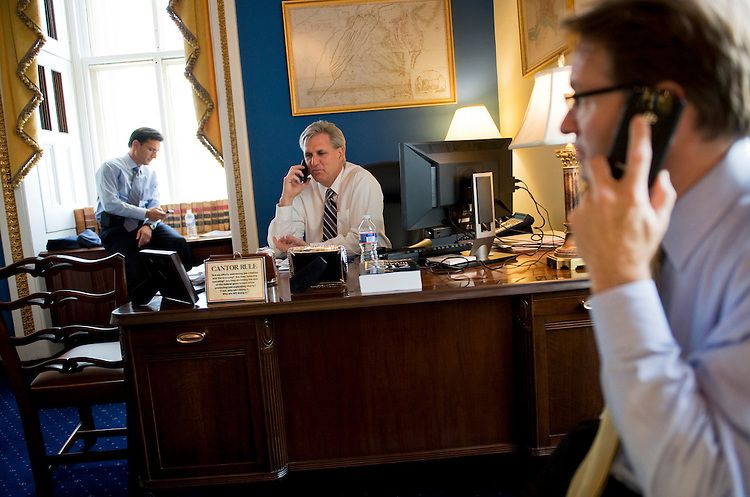 UNITED STATES - AUGUST 01:  From left, House Majority Leader Eric Cantor, R-Va., Majority Whip Kevin McCarthy, R-Calif., and Chief Deputy Whip Peter Roskam, R-Ill., phone members of their caucus from Cantor'ss Capitol office to see how they will be voting before the debt limit vote in the House, Monday.  (Photo By Tom Williams/Roll Call)