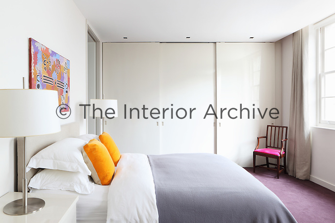 A double bed with lilac blanket and yellow cushions in a white bedroom with a built in wardrobe with sliding doors. Two metal lamps stand on bedside chests of drawers.