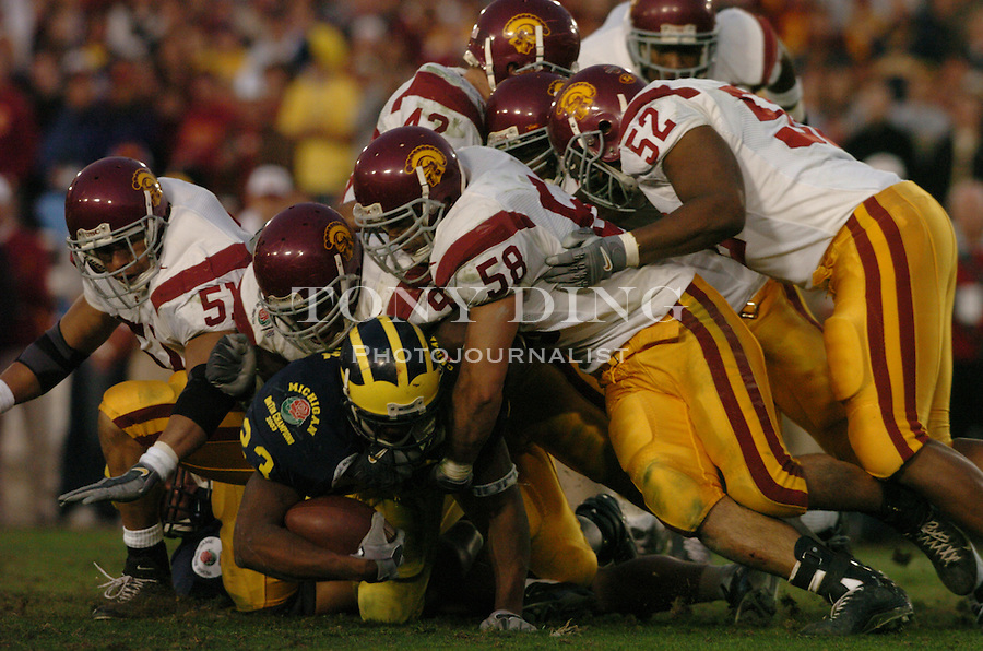 Michigan senior Chris Perry (23) is overpowered by the USC defensive line during the Wolverines' 14-28 loss to USC on Thursday, January 1, 2004 at the Rose Bowl in Pasadena, California. It was Michigan's 18th appearance at the Rose Bowl and the 90th game the bowl has played. (TONY DING/The Michigan Daily)
