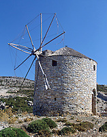 A large, sail-wing, horizontal-axis windmill, with its circular stone building intact, standing alone on a rocky hill against a brilliant, blue sky just off a back road on the Peloponnese Island. This style windmill dates back to the 1300s.