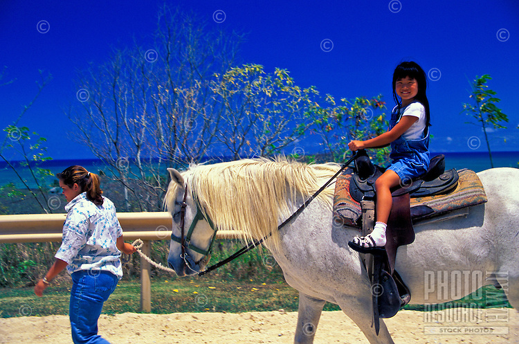 A child enjoys riding on a white horse in the corral at Kualoa Ranch's activity center on Oahu's Windward Side.