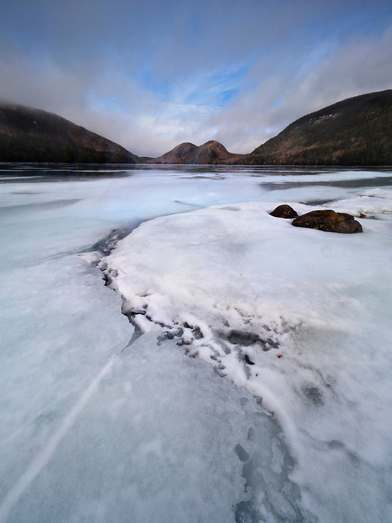 Passing winter storm clears over the Bubbles and a snow- and ice-covered Jordan Pond in Acadia National Park, Maine