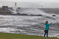 A woman takes pictures of the see while waves crash against the promenade wall of the Porthcawl lighthouse, caused by Storm Freya in south Wales, UK. Sunday 03 March 2019
