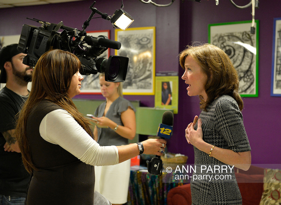 Bellmore, New York, USA. September 16, 2014. At right, KATHLEEN RICE, Democratic congressional candidate (NY-04), calls for congressional action both to pass legislation prohibiting employment discrimination on basis of sexual orientation and gender identity, and to totally repeal the Defense of Marriage Act. Channel 12 news, of Long Island, is video interviewing Rice, who first toured Pride for Youth, a division of the Long Island Crisis Center, which is a program that provides services for lesbian, gay, bisexual and transgender youth and their families. Rice is in her third term as Nassau County District Attorney.