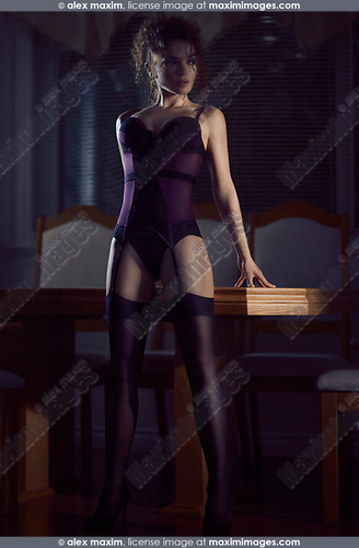 Sensual glamour portrait of a sexy beautiful woman wearing a purple corset and stockings standing in a bold confident femme fatale pose leaning against a table in dim night light