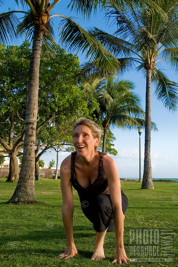 A woman practices yoga on the grass at Queens Beach Park in Waikiki with palms in the backround.